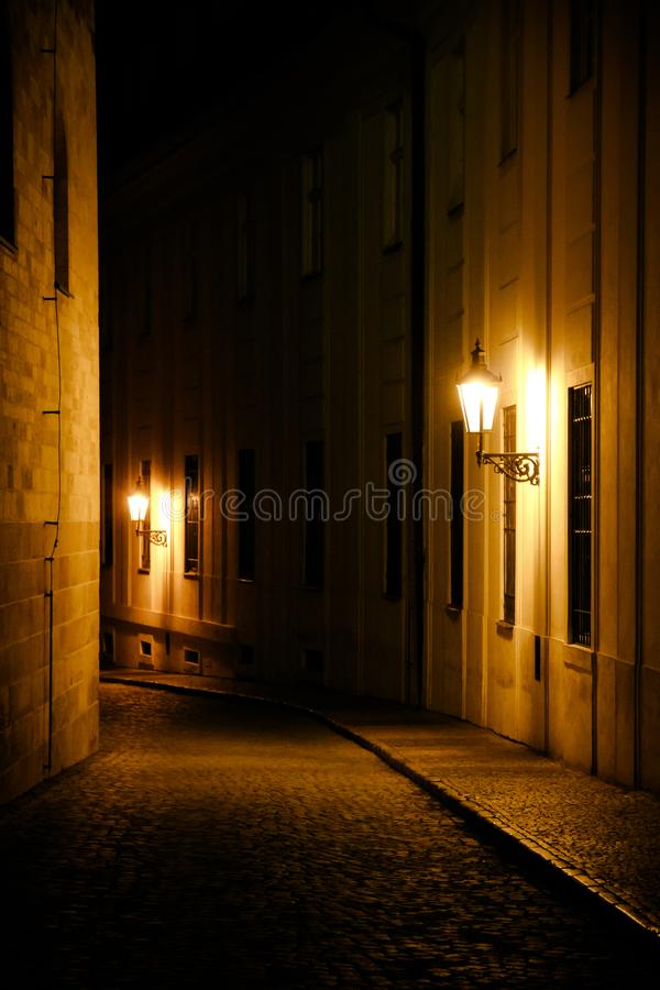 Old lanterns illuminating a dark alleyway medieval street at night in Prague, Czech Republic. Low key photo with brown yellow tone. S from the lanterns as single stock image