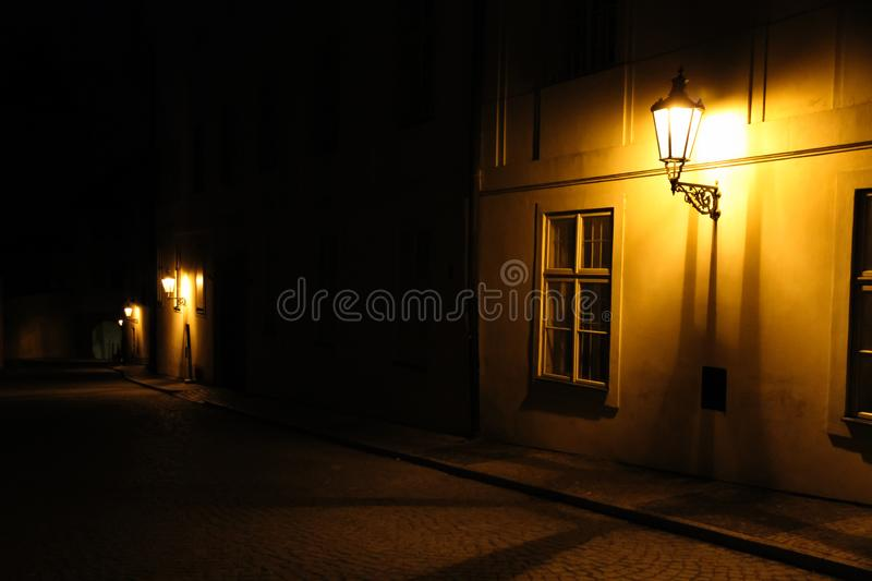 Old lanterns illuminating a dark alleyway medieval street at night in Prague, Czech Republic. Low key photo with brown yellow tone. S from the lanterns as single stock photo