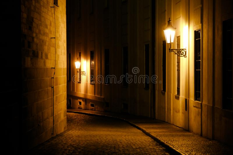 Old lanterns illuminating a dark alleyway medieval street at night in Prague, Czech Republic. royalty free stock image