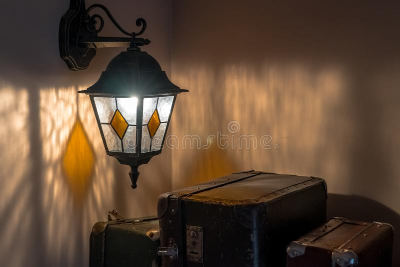 Old latern on a wall and suitcases stock image