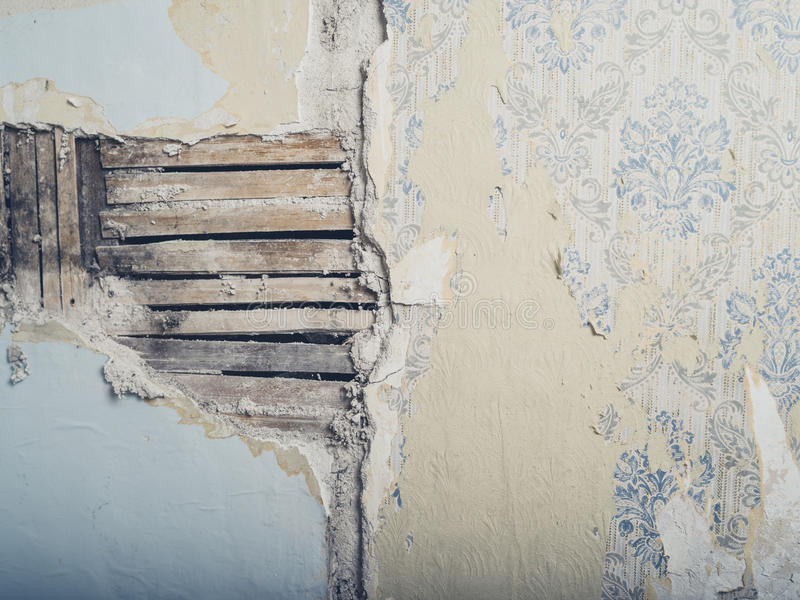 Old lath and plaster wall. An old lath and plaster wall with antique wallpaper stock photos