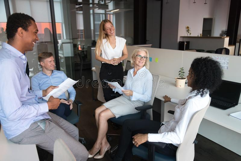 Old leader talking to team presenting work plan at meeting. Old female leader coach talking to happy sales team employees presenting work plan at group stand up stock photo