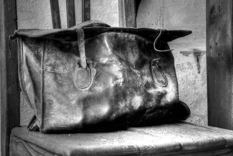 Old Leather Bag. On a chair royalty free stock photo