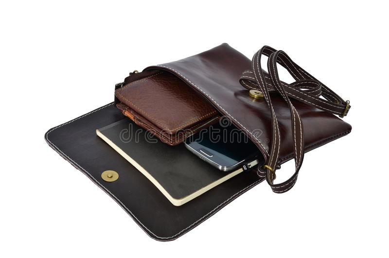 Old leather bag. With scratches and stains - opened showing pens and cell phone royalty free stock photo