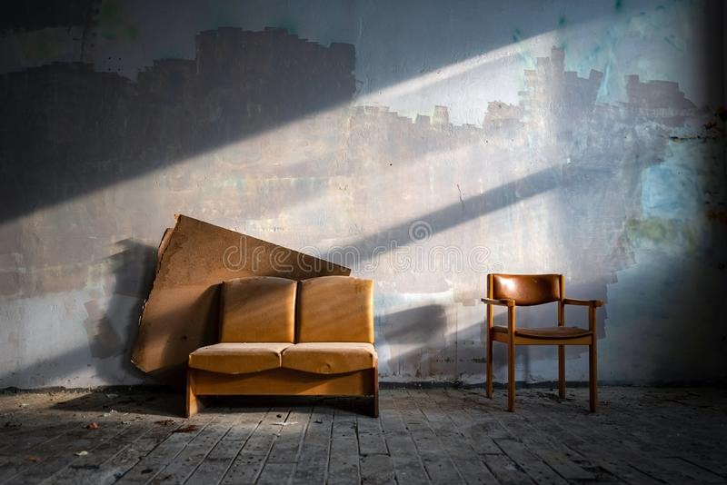 Old leather couch in abandoned factory building side lit by sun. Rustic furniture in haunted house royalty free stock photo