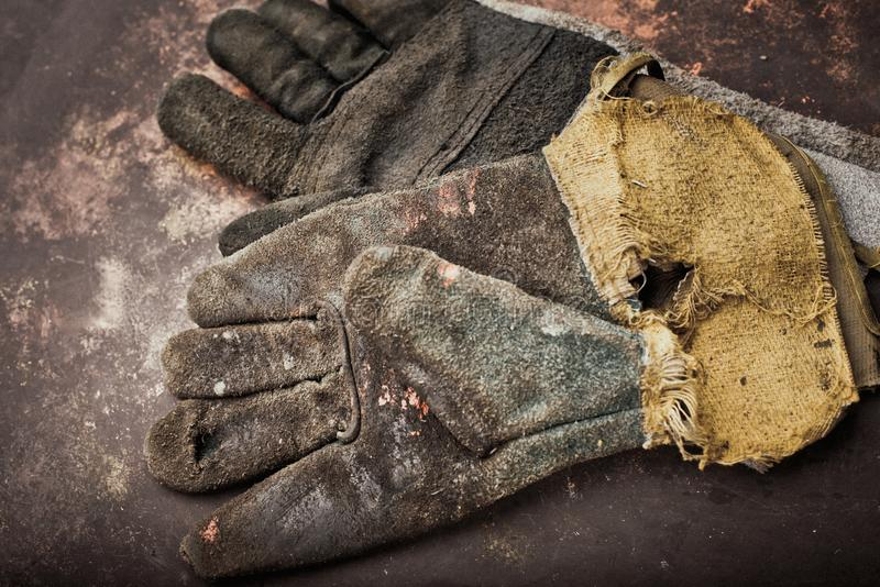 Old leather gloves for welders on rusty table royalty free stock photos