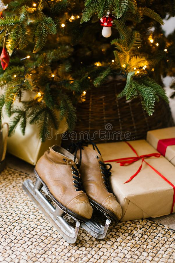Old leather skates under Christmas tree with gift. Boxes royalty free stock photography