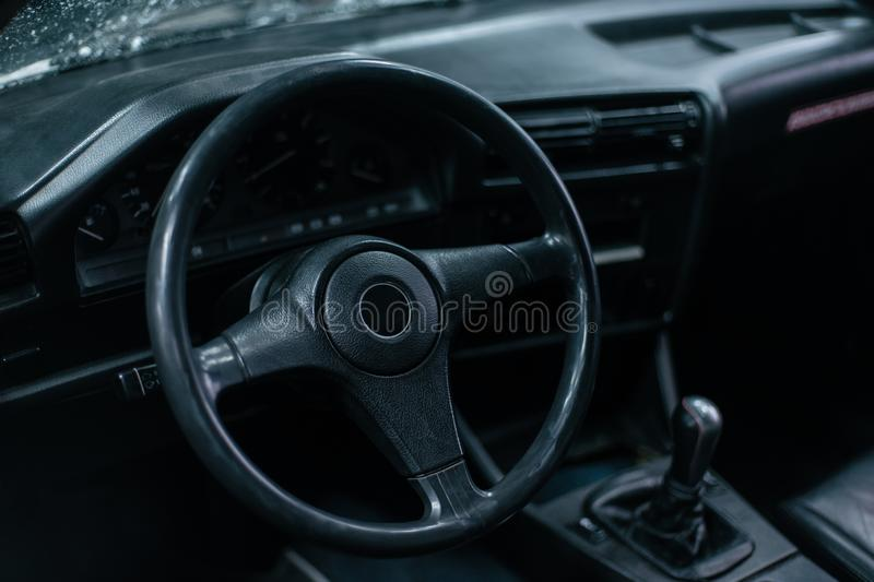 Old leather stylish sport steering wheel in old school sport car. With dark interior stock image