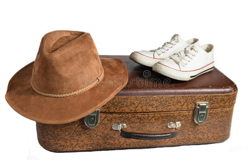 Old leather suitcase, retro sneakers, felt hat isolated on white background. royalty free stock photography