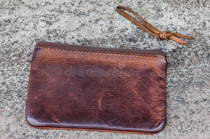 Old leather wallet. Old brown leather wallet on cement floor royalty free stock photo