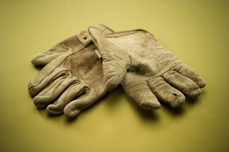 Old leather work gloves. Old tattered leather work gloves on a gold background royalty free stock photos