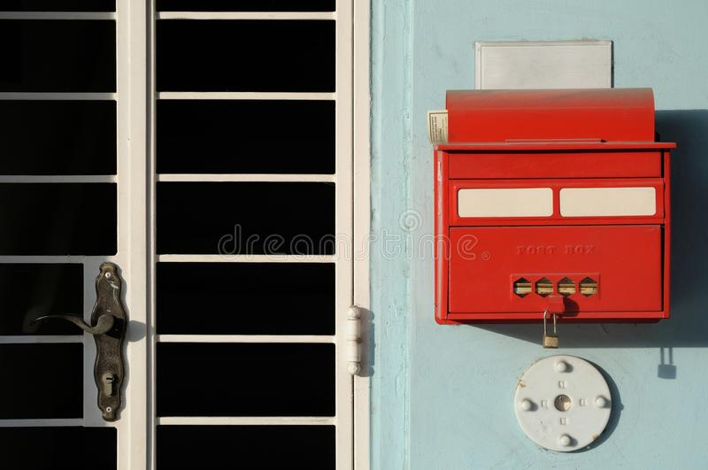 Old letter box. A red painted old letter box beside an apartment building gate royalty free stock image