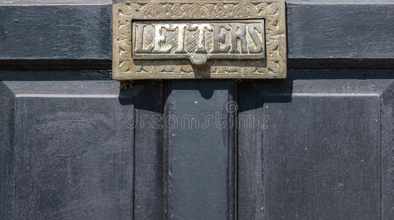 Old letterbox in the door, traditional way of delivering letters to the house, old mailbox. Correspondence stock photo