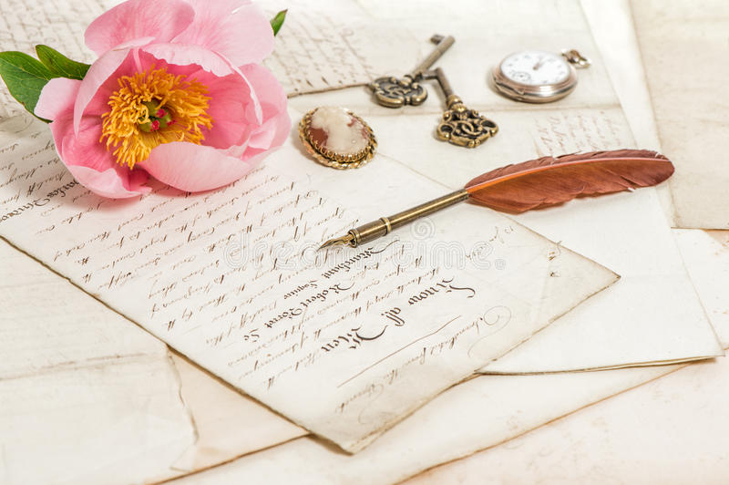 Old letters, pink peony flower and antique feather pen. Vintage. Old letters, pink rose peony flower and antique feather pen. romantic vintage background stock photography