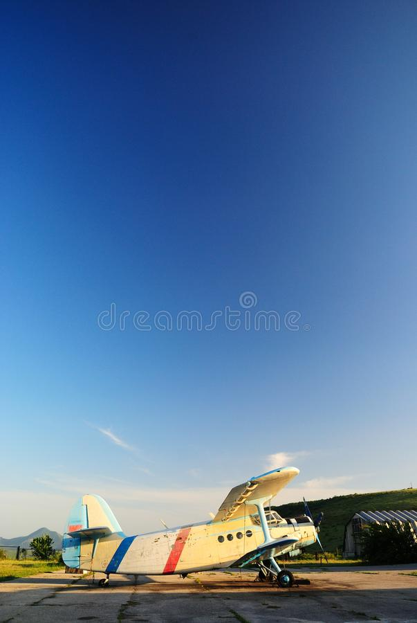 Old aircraft biplane against a blue sky. Old light aircraft biplane on the airfield against a clear blue sky royalty free stock photos