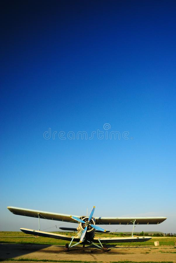 Old aircraft biplane against a blue sky. Old light aircraft biplane on the airfield against a clear blue sky royalty free stock photography