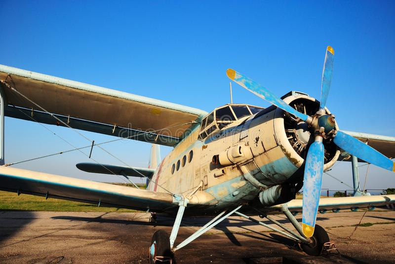 Old aircraft biplane against a blue sky. Old light aircraft biplane on the airfield against a clear blue sky royalty free stock images