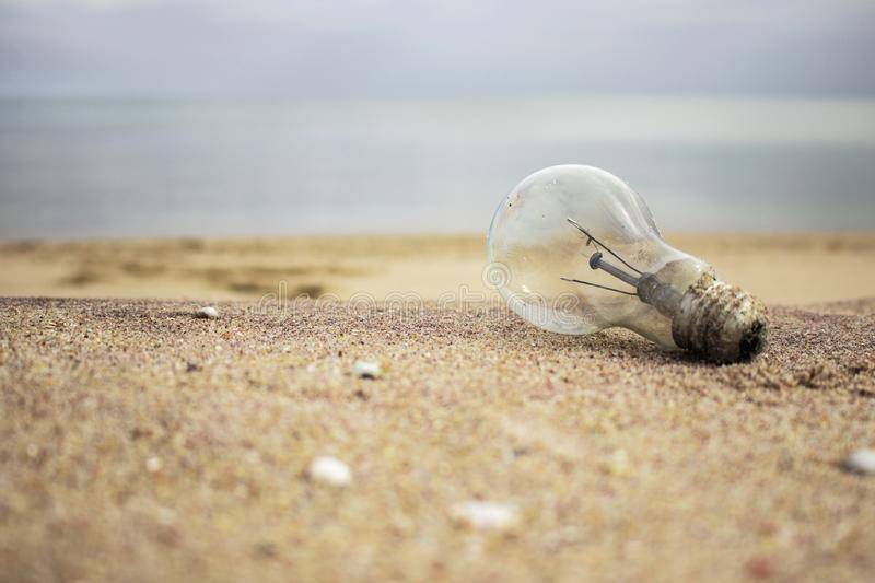 Old light bulb on the sand. Garbage on the beach. Ecological problem. Energy concent royalty free stock photo