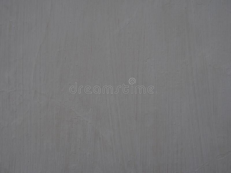 Old light grey painted wall surface with textured brush marks and faint cracks full frame background stock photos