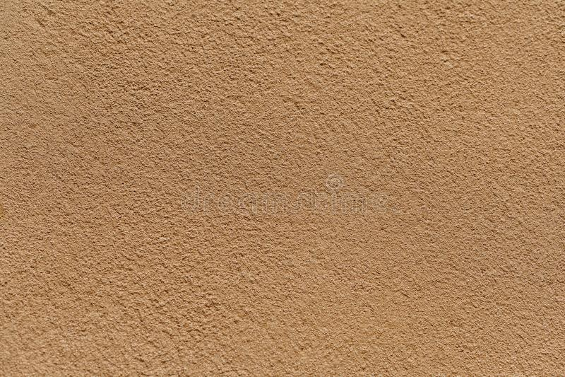 Old light sand wall covered with shabby uneven plaster. Texture of vintage golden stone surface royalty free stock photo