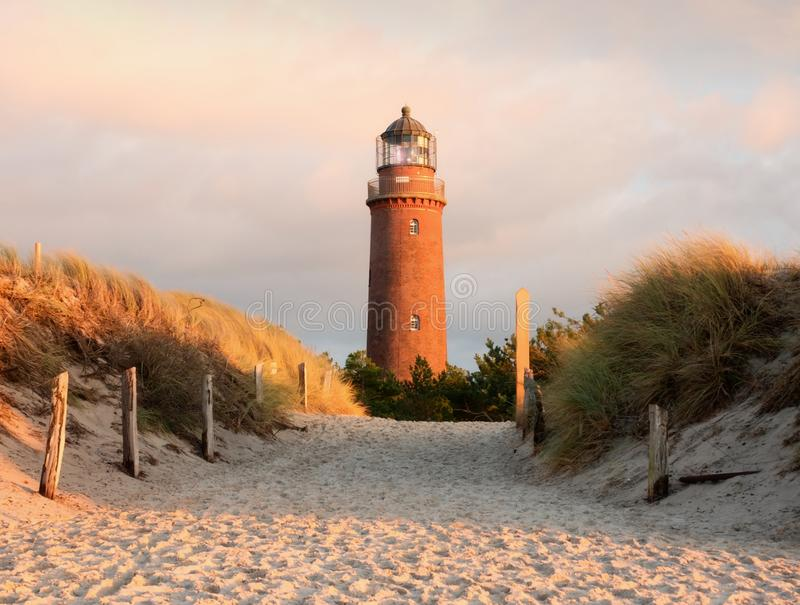 Old lighthouse above dunes and pine tree before sunset. Tower illuminated with strong warning light. Lighthouse built from red bricks, gallery with iron stock photo