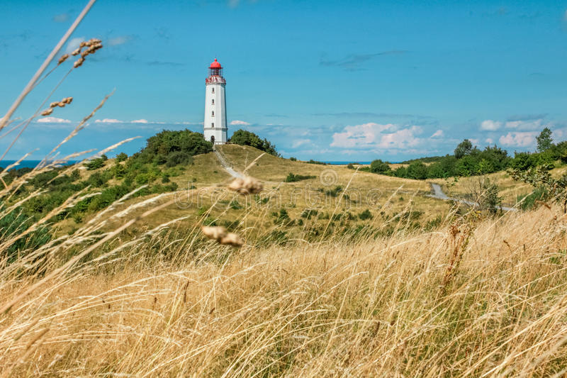 Old lighthouse Dornbusch on sunny summer day. Hiddensee, Baltic Sea. Old lighthouse Dornbusch on a grassy dune and people on top of the tower. Sunny summer day royalty free stock image