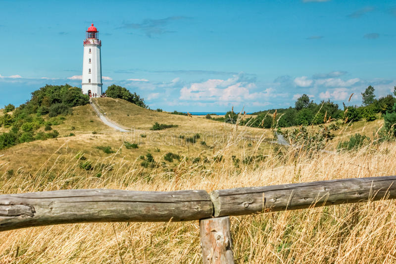 Old lighthouse Dornbusch on sunny summer day. Hiddensee, Baltic Sea. Old lighthouse Dornbusch on a grassy dune and people on top of the tower. Sunny summer day royalty free stock photography