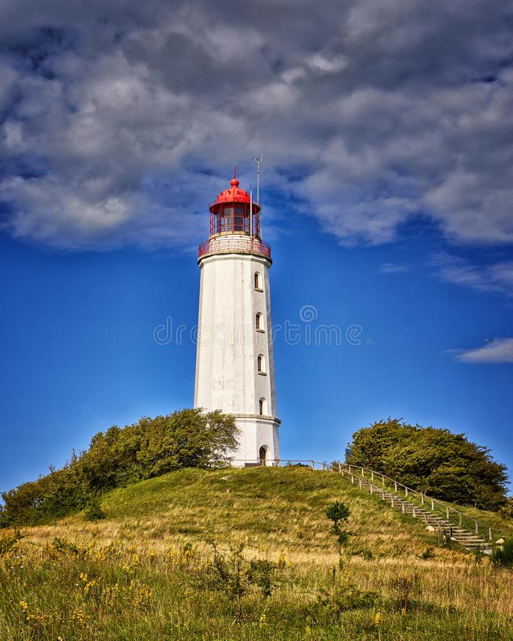 Old lighthouse Dornbusch on sunny summer day. Hiddensee, Baltic Sea. Clouds, island, landscape, nature, sky, water, germany, architecture, blue, building stock photography