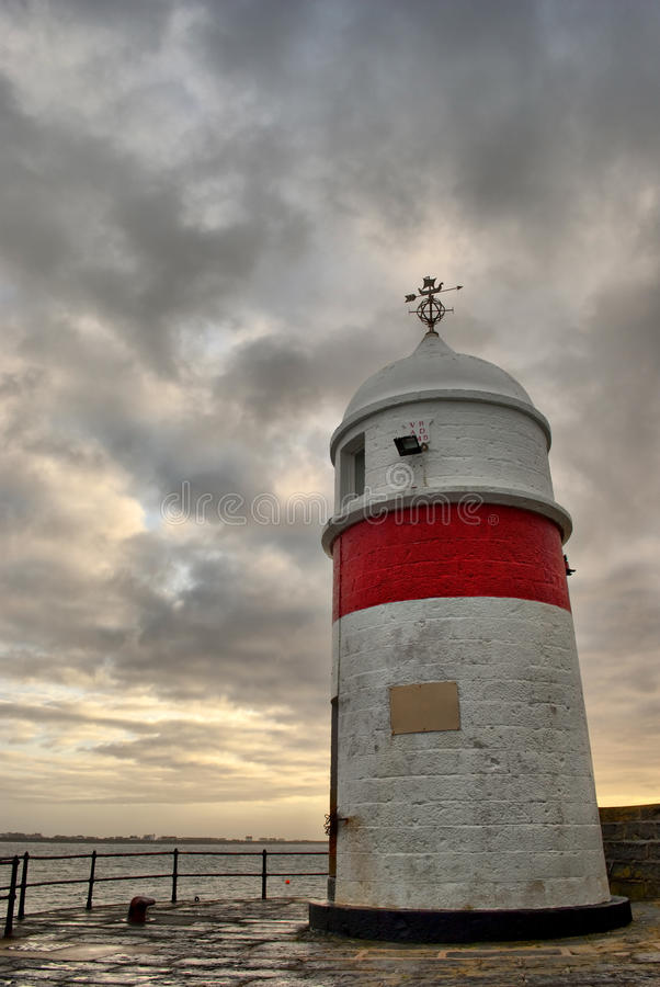 Old lighthouse with dramatic sky at dusk royalty free stock images