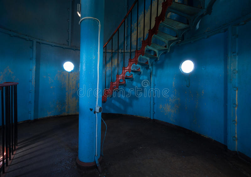 Small Round Windows: Old Lighthouse On The Inside. Red Iron Spiral Stairs