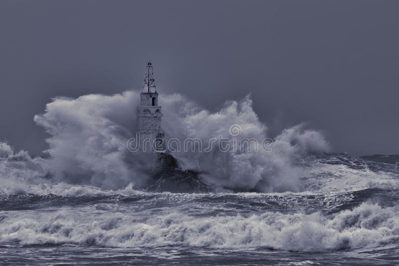 Old lighthouse in the middle of great stormy waves.Crashing big sea wave against rocks splash and spray .Huge stormy sea wave royalty free stock photography
