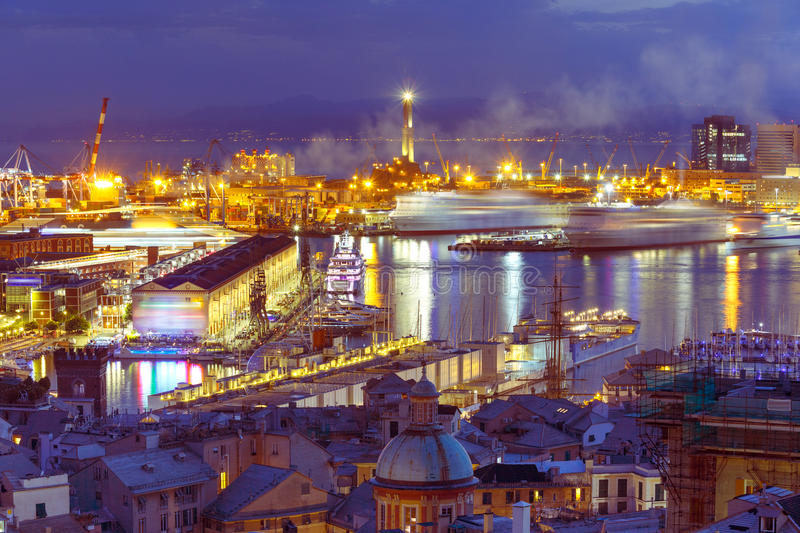 Old Lighthouse in port of Genoa at night, Italy. Historical Lanterna old Lighthouse, container and passenger terminals in seaport of Genoa on Mediterranean Sea stock photo