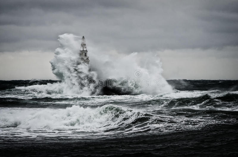 Old lighthouse in the sea in stormy day royalty free stock images