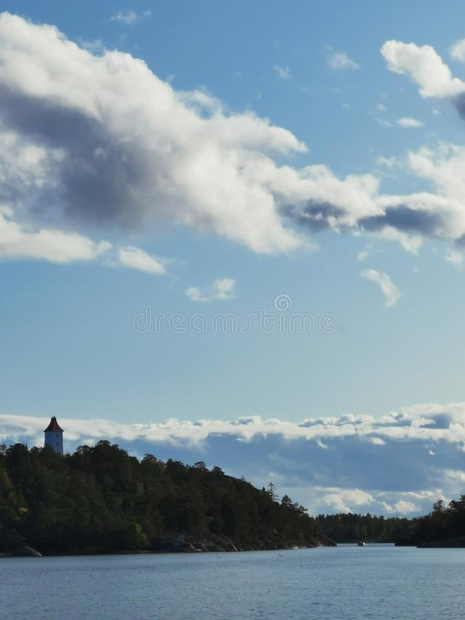 A old lighthouse in top of a hill surrounded with forest and blue sky and sea stock photography
