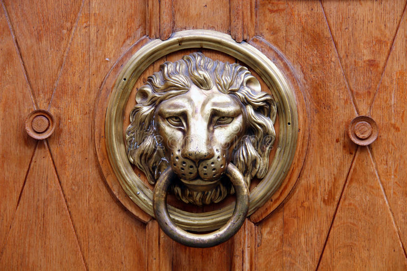 Old lion-head knocher on the wooden door stock images