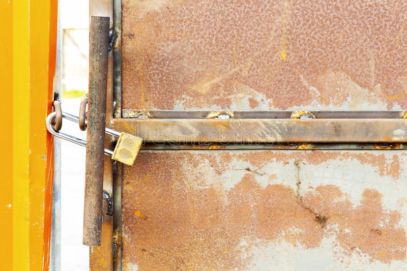 Old locked padlock on the gate of rusty metal steel of factory b royalty free stock image