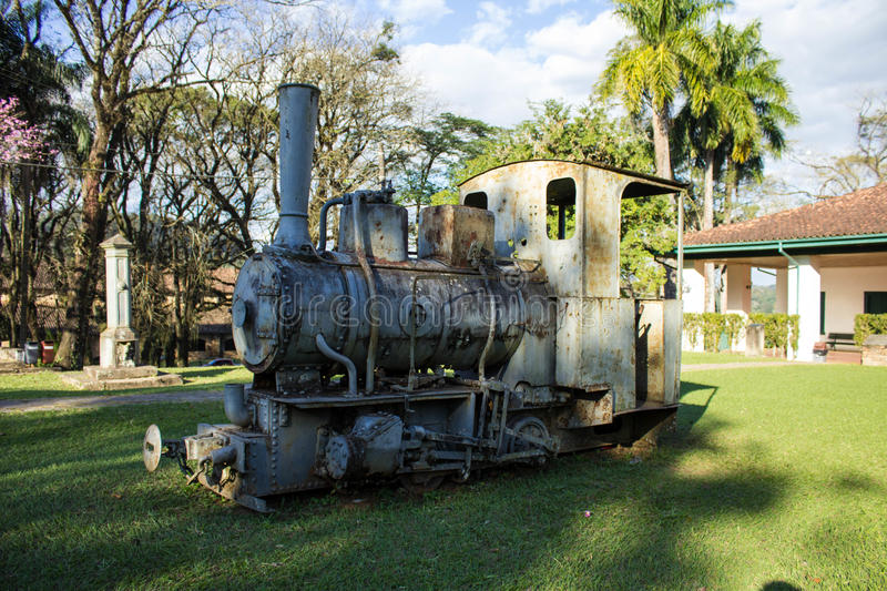 Old locomotive machine exposed in the garden. Of a ruined mansion stock image