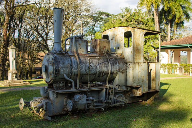 Old locomotive machine. In the grass and in the background an old house royalty free stock image