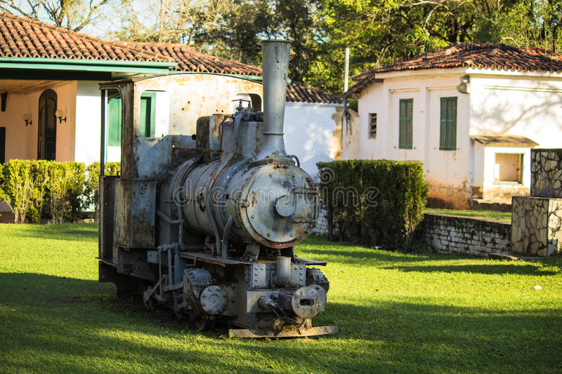 Old locomotive machine. In the grass and in the background an old house stock photography