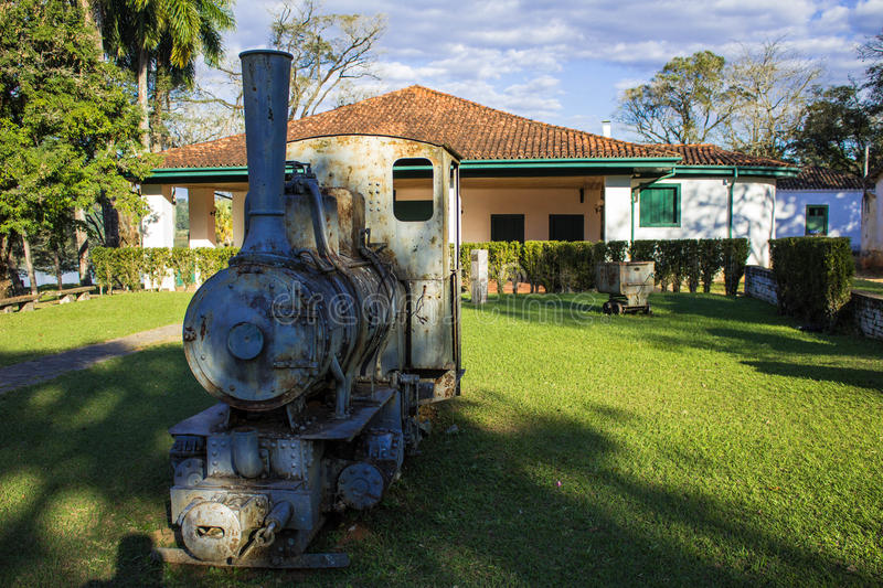 Old locomotive machine. In the grass and in the background an old house royalty free stock photography