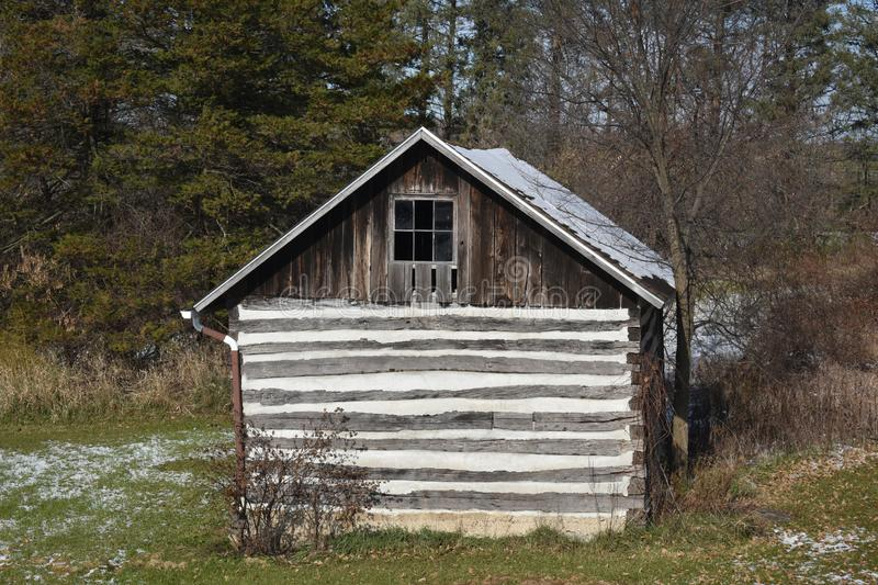 Old log cabin storage building in the woods in early winter light snow royalty free stock photos