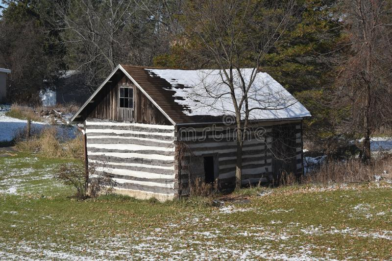 Old log cabin storage building in the woods with light snow in winter stock photos