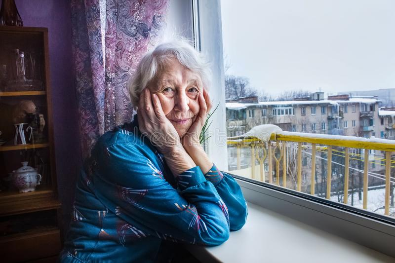 Old lonely woman sitting near the window in his house. royalty free stock photos