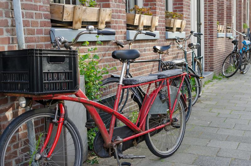 Old long Red vintage bike with two seats more behind the driver and big plastic box in front of him. Street view in Amsterdam, stock photos