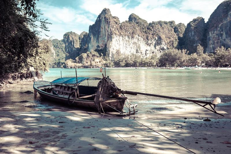 An old long-tailed boat made of wood at low tide. Depressive colors, tropical sandy beach stock image