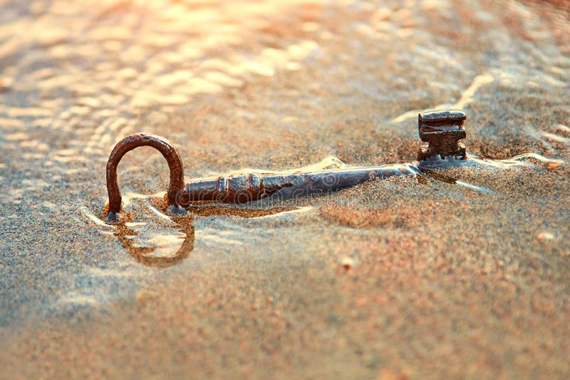 An old lost key in the sand is a newfound opportunity. The concept of success, luck and unexpected wealth.  stock images