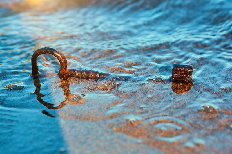 An old lost key in the sand is a newfound opportunity. The concept of success, luck and unexpected wealth.  stock photography