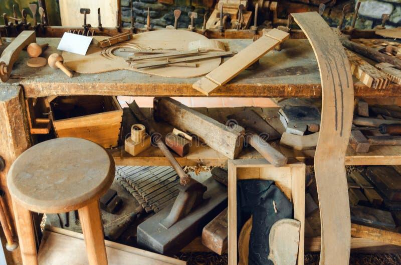 Old luthier`s workshop bench. Old luthier`s bench in a workshop of a guitar maker craftsman stock photo