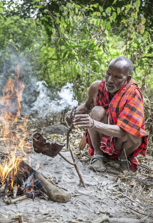 Old maasai man cooking meat on fire royalty free stock photo