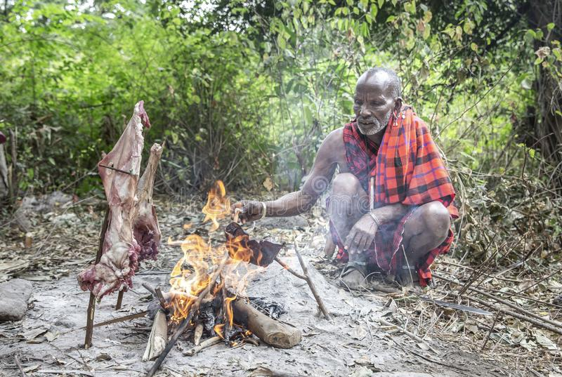 Old maasai man cooking meat on fire royalty free stock image